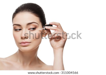 Beautiful young woman applying anti-ageing moisturizing serum to under eye area. Isolated over white background. Copy space. - stock photo