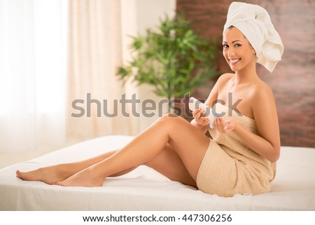 Beautiful young woman applying body lotion. Looking at camera