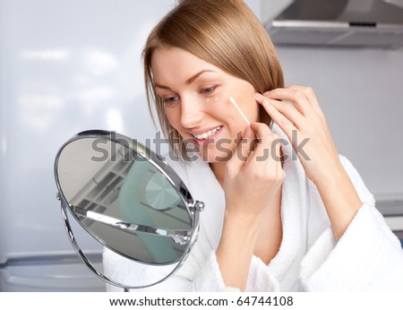 beautiful young woman applying cream on her face at home