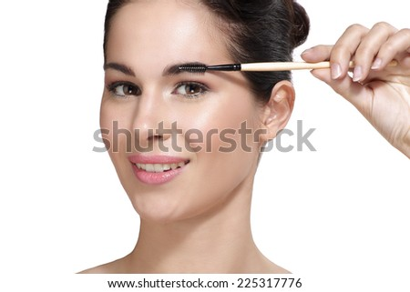 Beautiful young woman applying eyebrow brush on white - stock photo