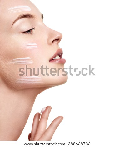 Beautiful Young Woman applying facial moisturizing cream.Skincare concept - stock photo