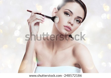 Beautiful young woman applying foundation on her face with tassel, skin care concept / photoset of attractive brunette girl on blurred background with bokeh   - stock photo