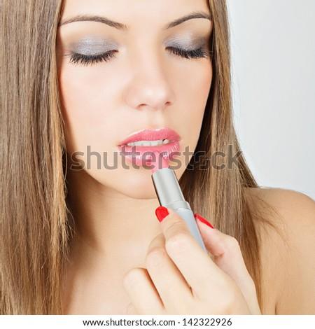 Beautiful young woman applying lipstick - stock photo