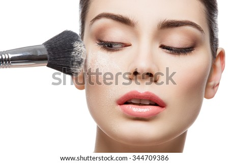 Beautiful young woman applying loose face powder with brush. Macro shot. Isolated over white background. Copy space. - stock photo