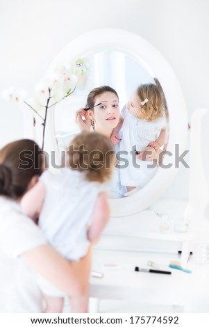 Beautiful young woman applying make up and her toddler daughter watching it in a white bedroom with an elegant dresser with a round mirror - stock photo