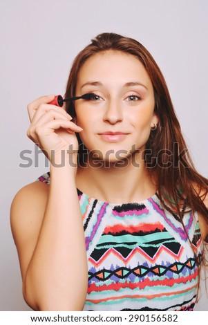 Beautiful young woman applying mascara. Make-up concept. - stock photo
