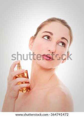 Beautiful young woman applying perfume on her neck  - stock photo