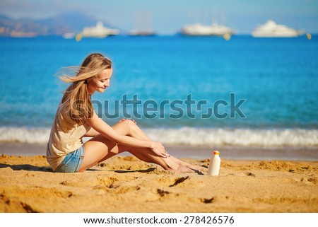 Beautiful young woman applying sunscreen on her legs  - stock photo