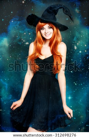 Beautiful young woman as halloween witch with scroll-magical portrait - stock photo