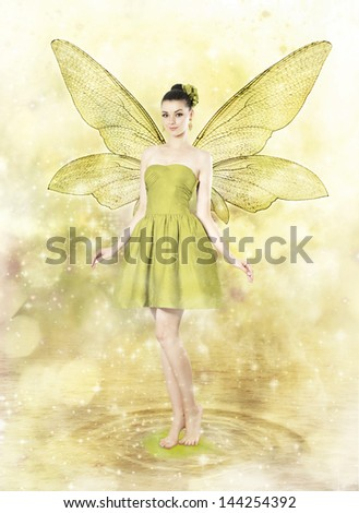 Beautiful young woman as spring fairy on golden magical background - stock photo