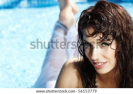 Beautiful young woman at a pool - stock photo