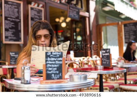 Beautiful young woman at a typical french restaurant