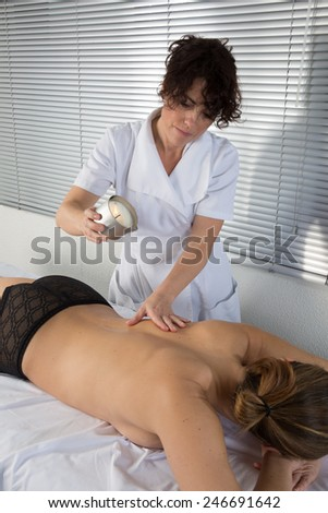 Beautiful young woman at beauty salon spa getting a body oil treatment.