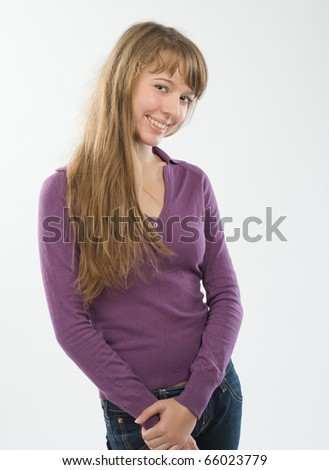Beautiful young woman at studio over plain background