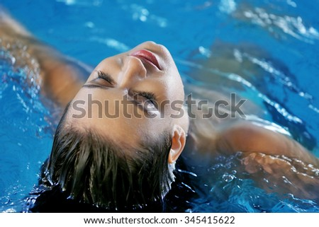 Beautiful young woman at swimming pool