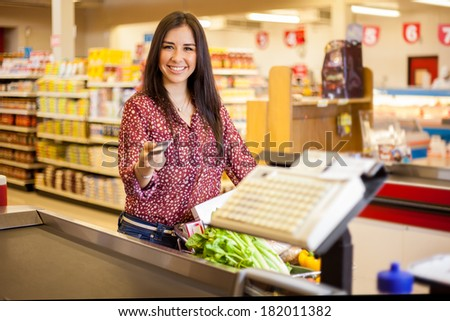 Beautiful young woman at the cash register of a supermarket paying with a credit card and smiling - stock photo