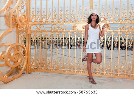 Beautiful young woman at the golden gates of the Palace of Versailles in Paris, France. - stock photo