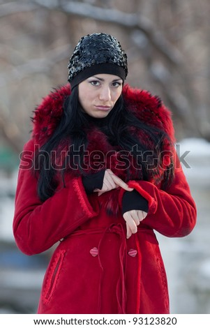 Beautiful young woman at winter. Attractive brunette in red checking time in the winter park - stock photo