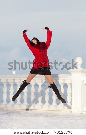 Beautiful young woman at winter. Attractive brunette in red jumping in the winter park