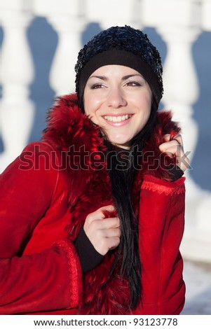 Beautiful young woman at winter. Portrait of young beautiful brunette in the winter park. Girl looking at camera smiling - stock photo