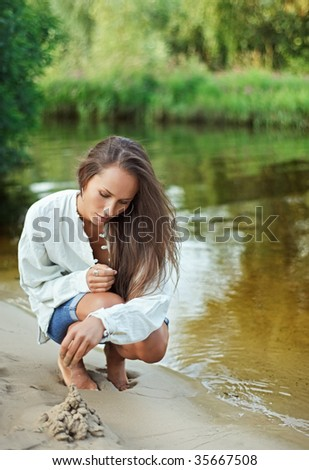 Beautiful young woman bilding sand castle - stock photo