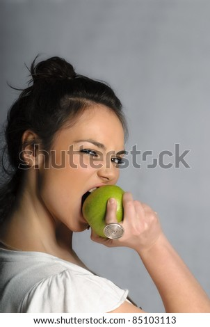 Beautiful young woman biting an apple portrait isolated