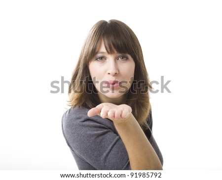 Beautiful young woman blowing a kiss, isolated on a white background - stock photo