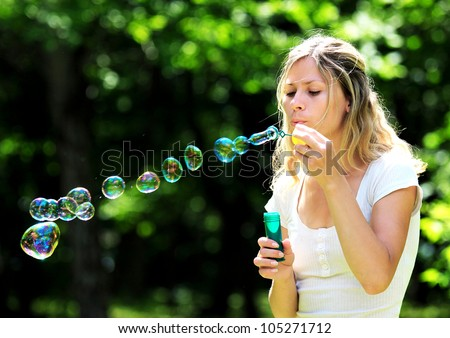 beautiful young woman blowing bubbles outdoors