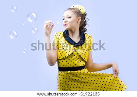 beautiful young woman blowing soap bubbles on blue background - stock photo