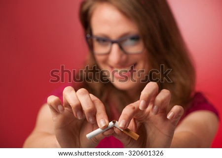 beautiful young woman breaks a cigarette as a gesture for quit smoking - stock photo