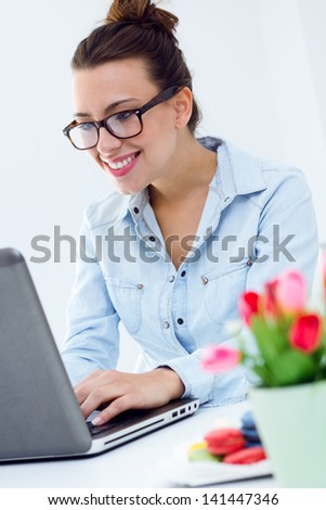 beautiful young woman browsing internet at home - stock photo