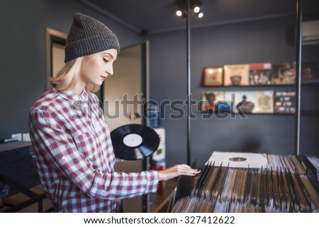 beautiful young woman browsing records in the vinyl record store - stock photo