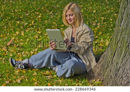 Beautiful young woman browsing tablet in the park while sitting on the grass. - stock photo
