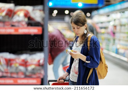 Beautiful young woman buying food at supermarket  - stock photo