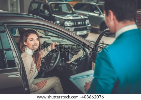 Beautiful young woman buys a car in the dealership saloon. - stock photo