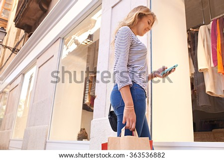 Beautiful young woman by fashion store window using smartphone to network, smiling outdoors. Adolescent holiday and technology lifestyle, clothing shopping street exterior. Travel and recreation. - stock photo