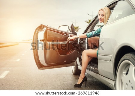 Beautiful young woman came out from the car on road - stock photo