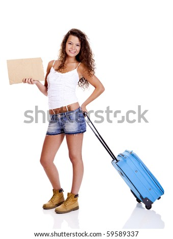 Beautiful young woman carrying a blue suitcase and holding a cardboard, isolated on white background - stock photo