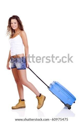 Beautiful young woman carrying a blue suitcase, isolated on white background - stock photo