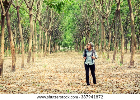 Beautiful young woman carrying backpack walking in forest  - stock photo