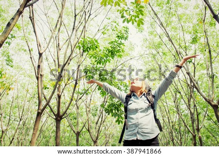 Beautiful young woman carrying backpack walking in forest raising her hands happy with fresh air - stock photo