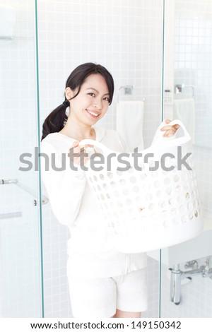 beautiful young woman carrying laundry basket