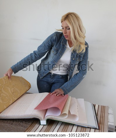 Beautiful young woman chooses wallpaper - stock photo