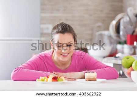 Beautiful young woman choosing between fruits and sweets. She is in kitchen. - stock photo