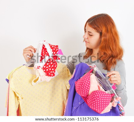 Beautiful young woman choosing clothes - stock photo
