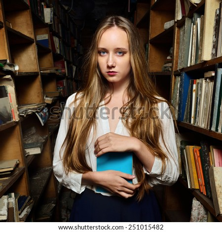 Beautiful young woman choosing the book in library. - stock photo