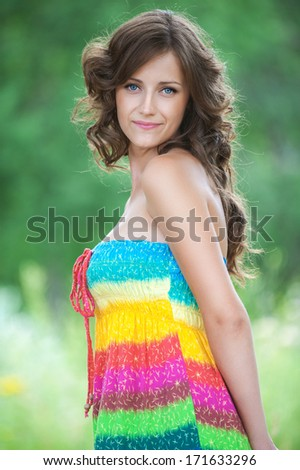 Beautiful young woman close-up in colorful dress, against green of summer park. - stock photo