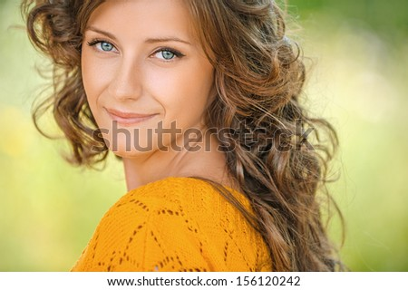 Beautiful young woman close-up in orange sweater, against green of summer park. - stock photo