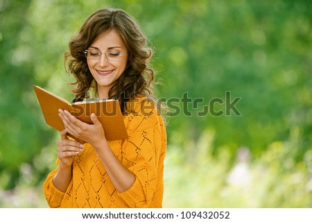 Beautiful young woman close-up in orange sweater reading book, against green of summer park.