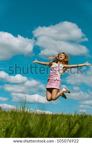 Beautiful young woman close-up jumping, against green of summer park and blue sky. - stock photo